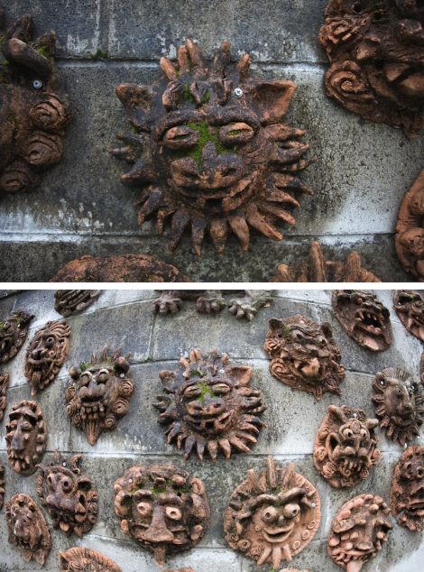 shisa faces on a stone wall