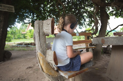 day 163 | Eden listening to the audio guide, Killing Fields of Choeung Ek, Phnom Penh, Cambodia